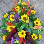 Grabstrauß mit Sonnenblumen und Lilien