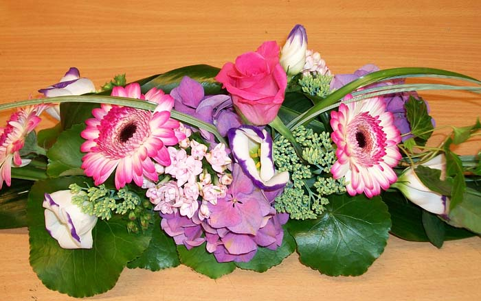 Bunter Tischschmuck mit Rosen, Gerbera und Hortensien